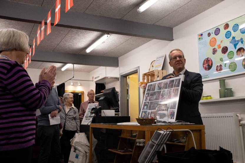 Michael Trinskjær, chef for kommunikation og engagement i Danmission, overrækker en fotocollage til butikkens frivillige og takker for deres dedikerede indsats.